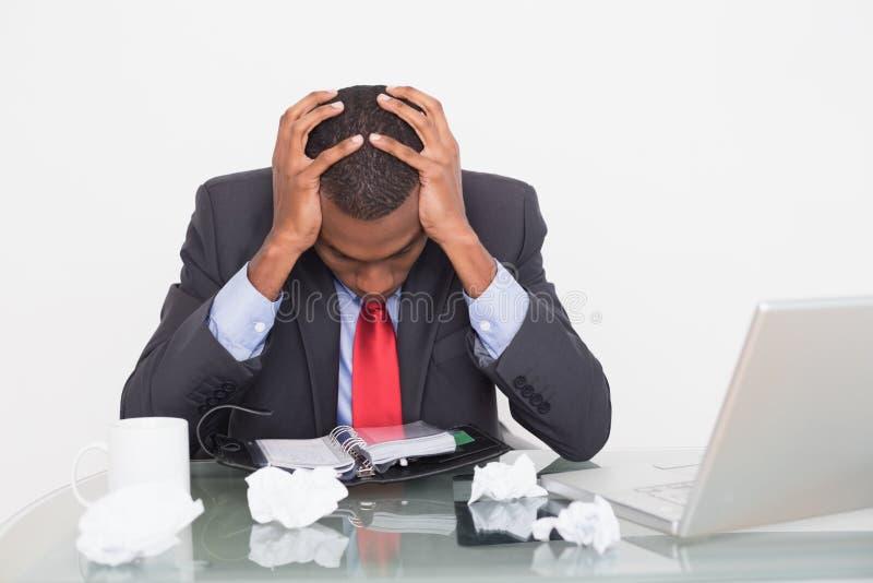 Uomo d'affari frustrato di afro con la testa in mani allo scrittorio fotografia stock libera da diritti