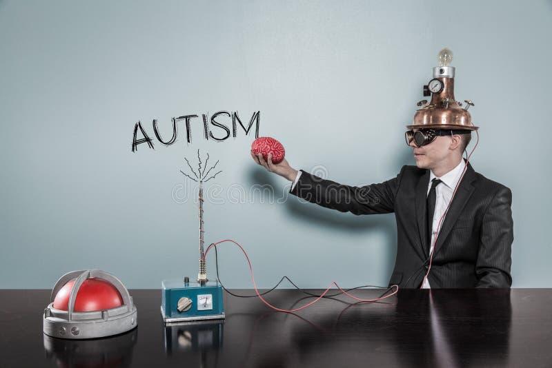 Uomo d'affari In Futuristic Helmet che tiene Brain By Autism Text fotografie stock