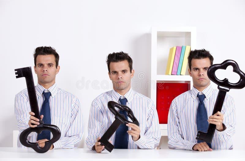 Uomo d'affari gemellare tre che tiene un tasto gigante fotografia stock libera da diritti