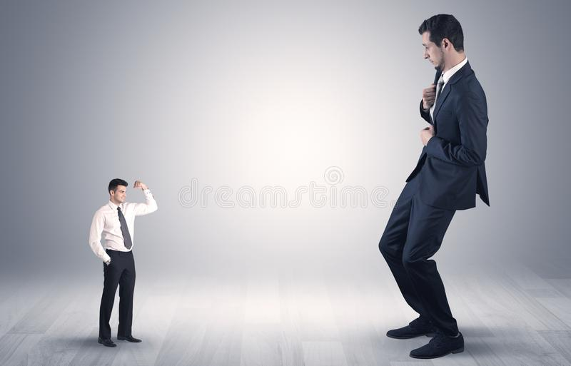 Uomo d'affari gigante spaventato del piccolo imprenditore fotografia stock