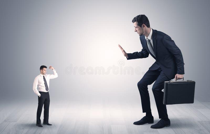Uomo d'affari gigante spaventato del piccolo imprenditore immagine stock libera da diritti
