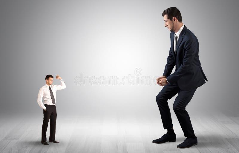 Uomo d'affari gigante spaventato del piccolo imprenditore immagini stock