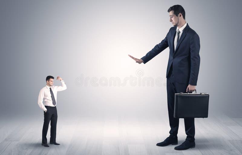Uomo d'affari gigante spaventato del piccolo imprenditore immagine stock