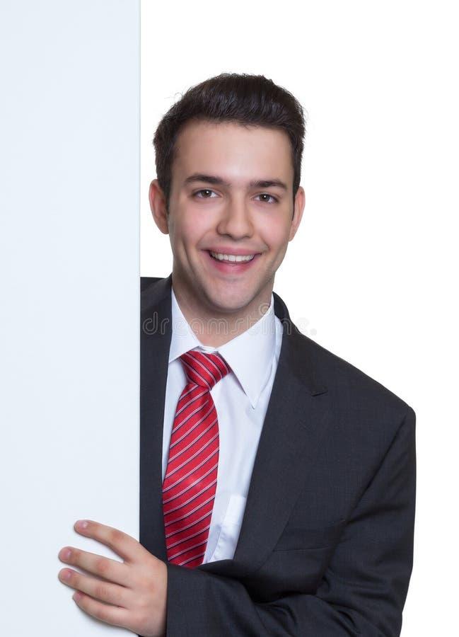Uomo d'affari giovane di risata dietro un bordo bianco immagini stock