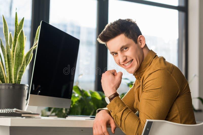 uomo d'affari giovane felice che celebra successo al posto di lavoro ed allo sguardo fotografia stock libera da diritti