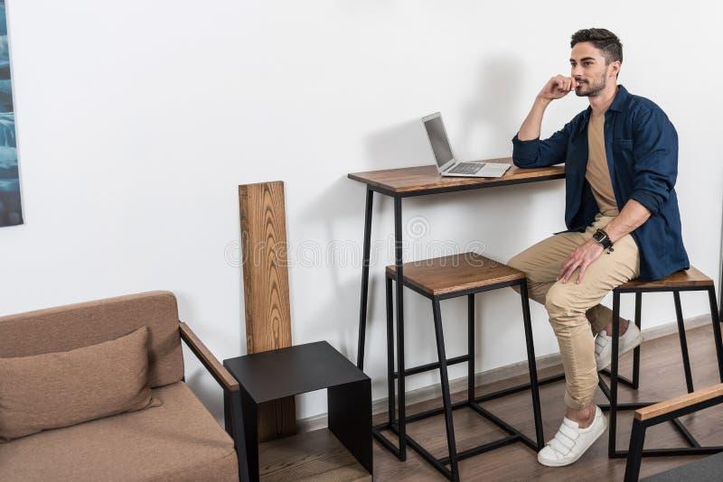 Uomo d'affari giovanile premuroso che lavora a casa tramite computer portatile fotografie stock