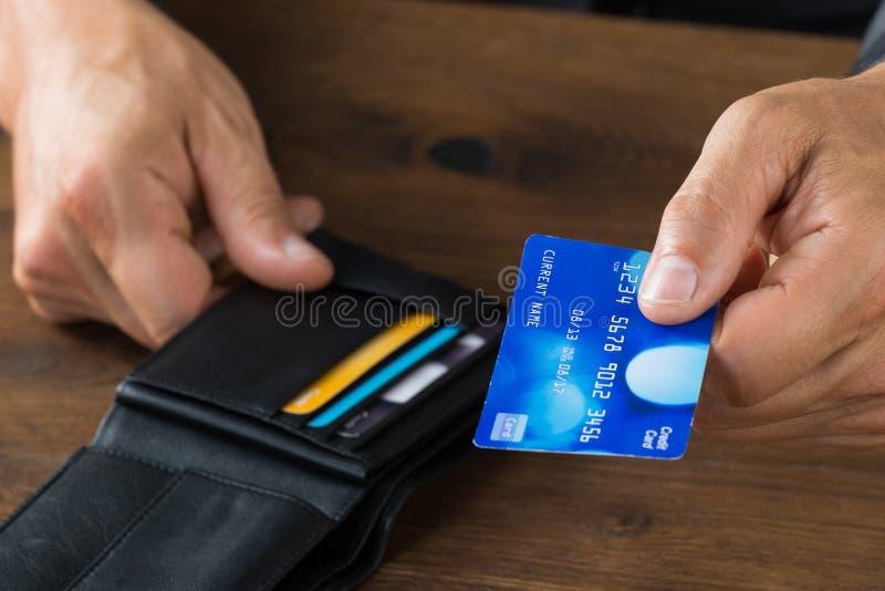 Uomo d'affari Giving Credit Card dal portafoglio fotografia stock libera da diritti