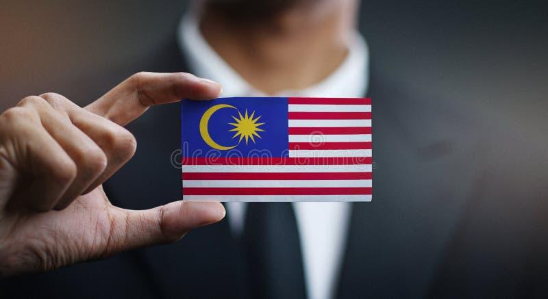 Uomo d'affari Holding Card della bandiera della Malesia immagini stock libere da diritti