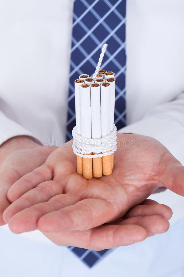 Uomo d'affari Holding Cigarettes Tied con la corda e lo stoppino immagini stock libere da diritti