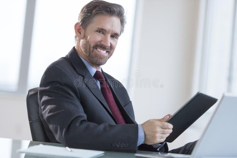 Uomo d'affari Holding Digital Tablet allo scrittorio fotografie stock