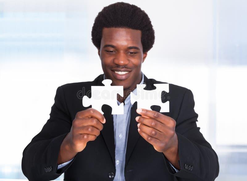 Uomo d'affari Holding Jigsaw Puzzle fotografia stock libera da diritti