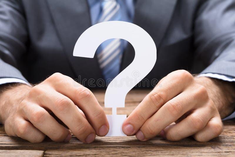 Uomo d'affari Holding Paper Question Mark At Table immagini stock