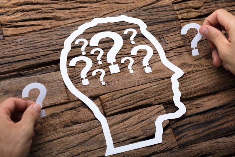 Uomo d'affari Holding Question Marks dal profilo della testa della carta fotografie stock libere da diritti