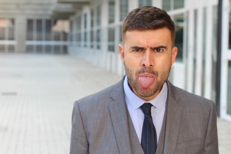 Uomo d'affari infastidito che attacca la sua lingua fuori fotografia stock