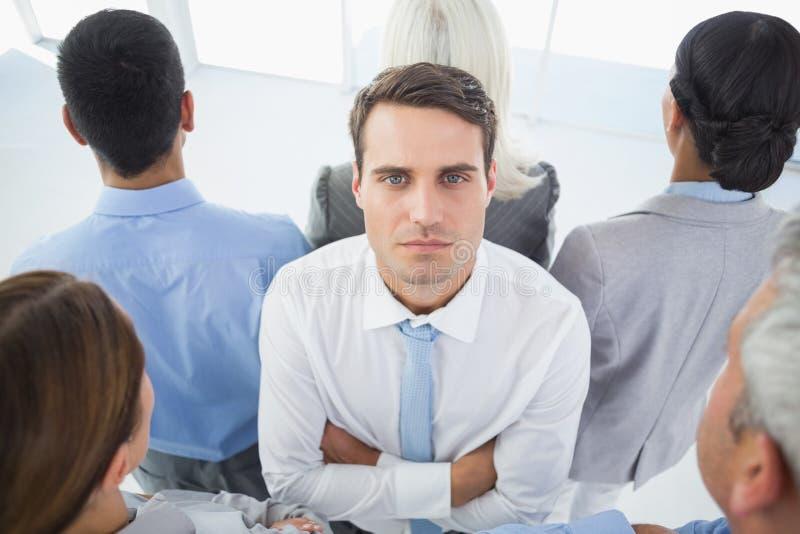 Uomo d'affari infelice che esamina macchina fotografica con il suo collega intorno lui fotografie stock libere da diritti