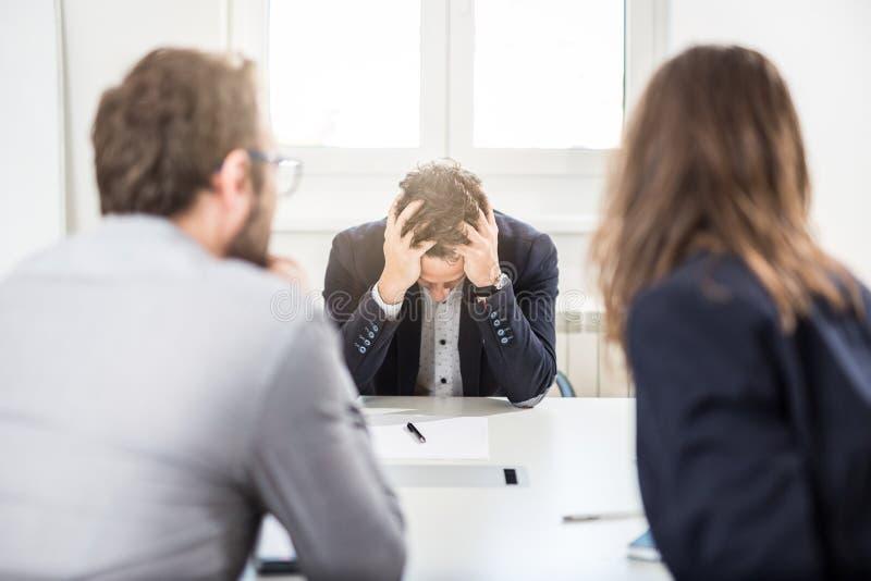 Uomo d'affari infelice con i suoi colleghi che si siedono allo scrittorio su una riunione nell'ufficio fotografie stock libere da diritti