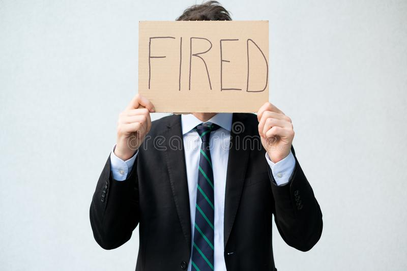 Uomo d'affari infornato che nasconde il suo fronte con il licenziamento fotografia stock
