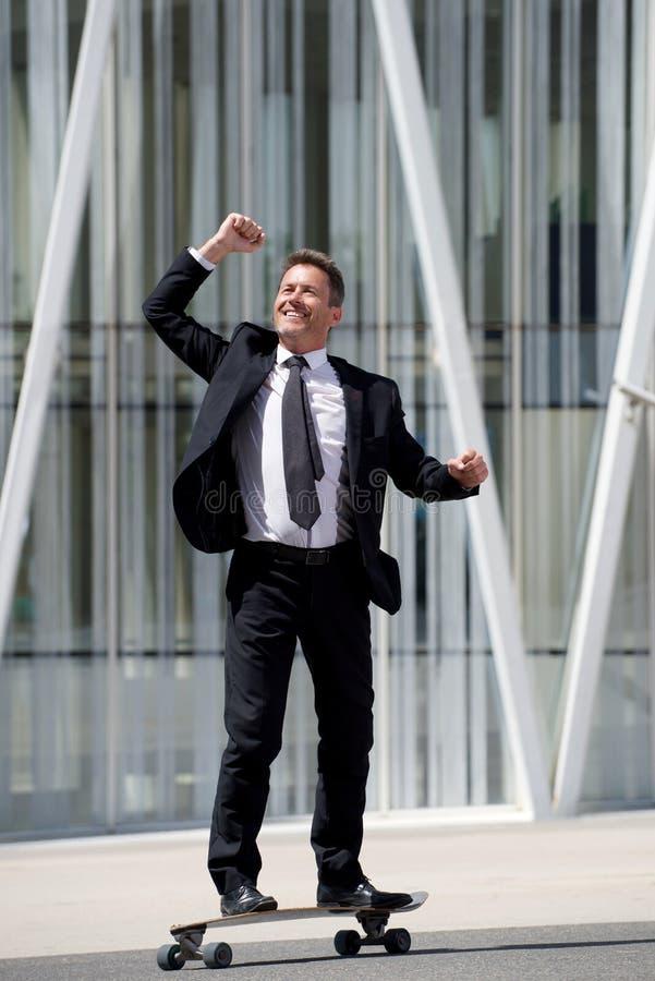 Uomo d'affari integrale di divertimento che sta sul pattino con il braccio steso fotografia stock libera da diritti