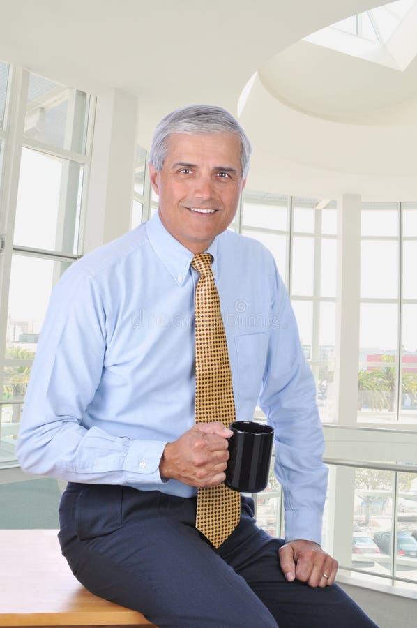 Uomo d'affari invecchiato centrale che si siede sul caffè dello scrittorio fotografie stock