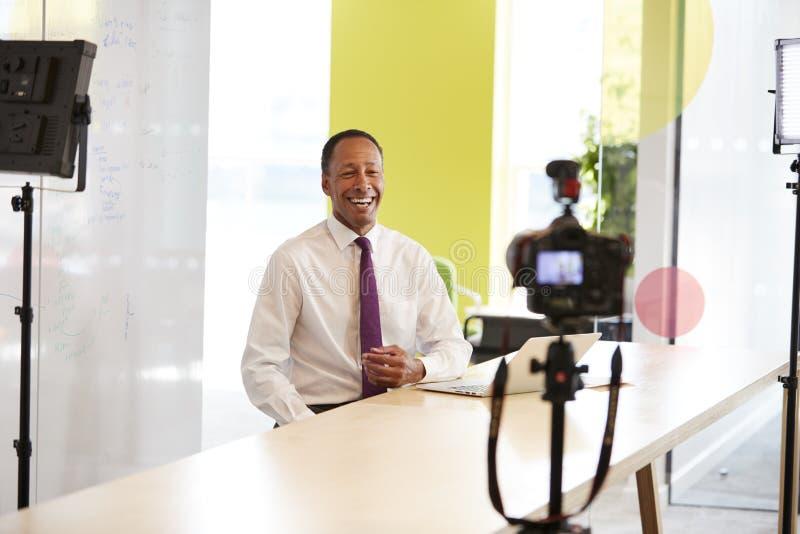 Uomo d'affari invecchiato mezzo che fa un video corporativo fotografia stock
