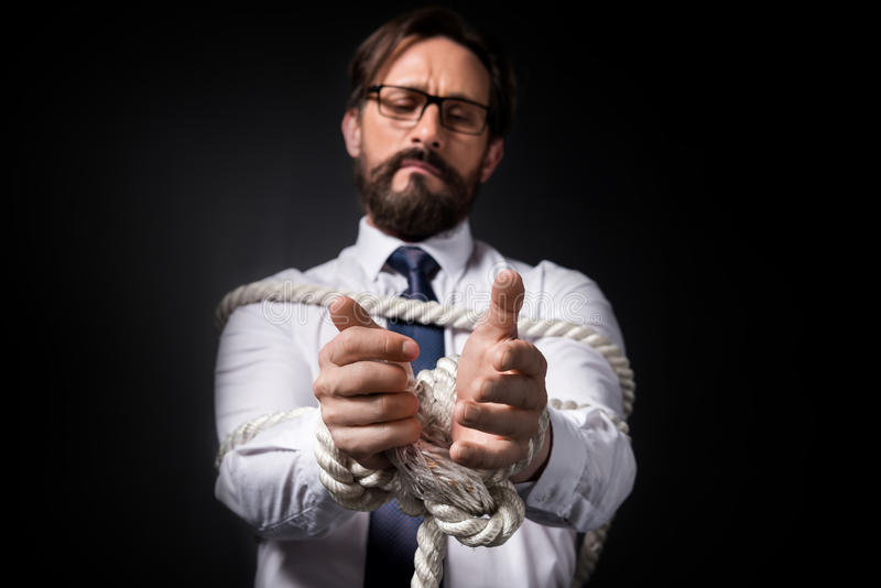 Uomo d'affari invecchiato mezzo turbato in occhiali che stanno legati con la corda immagini stock libere da diritti
