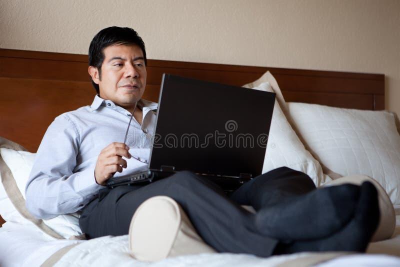 Uomo d'affari ispanico che per mezzo del computer portatile fotografia stock