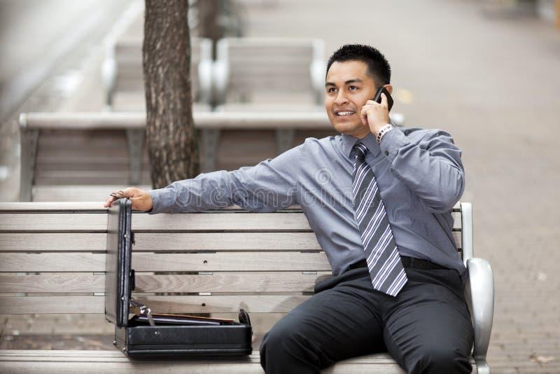 Uomo d'affari ispanico - comunicando sul telefono delle cellule fotografia stock libera da diritti