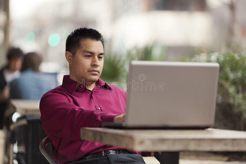 Uomo d'affari ispanico - funzionamento del computer portatile del caffè immagini stock libere da diritti