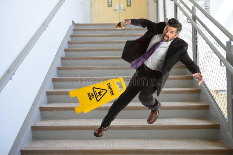 Uomo d'affari ispano Falling sulle scale fotografia stock