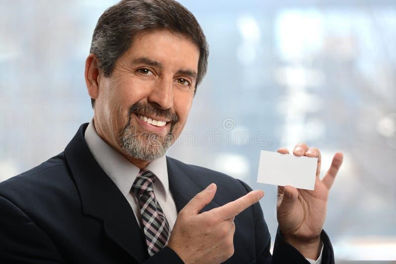 Uomo d'affari ispano Pointing al biglietto da visita immagini stock libere da diritti