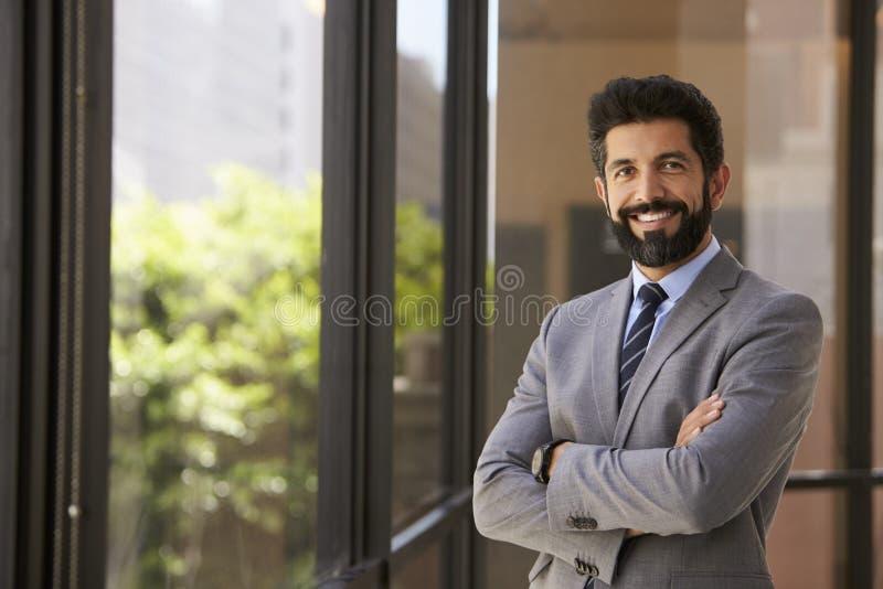 Uomo d'affari ispano sorridente con le armi attraversate, alla macchina fotografica fotografia stock