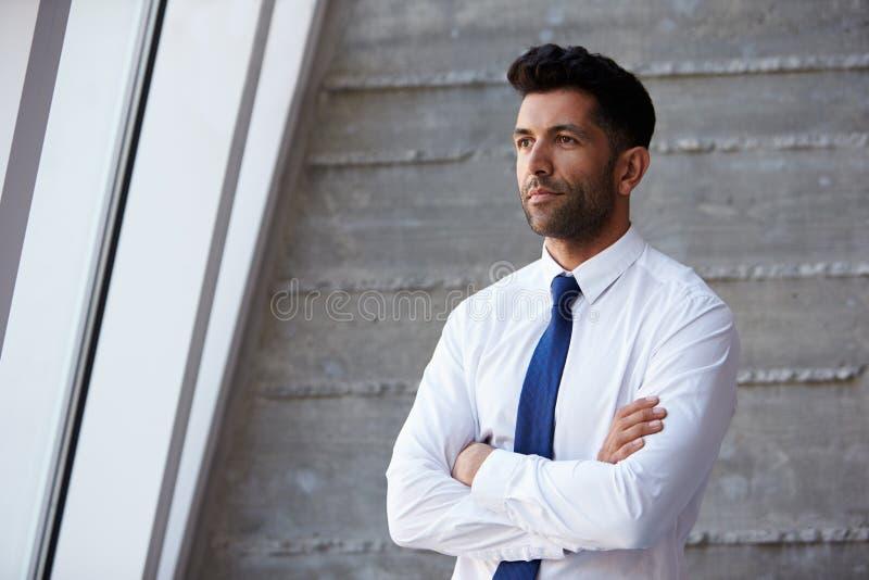 Uomo d'affari ispano Standing Against Wall in ufficio moderno fotografia stock