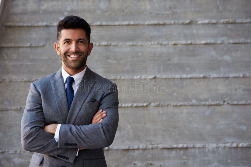 Uomo d'affari ispano Standing Against Wall in ufficio moderno immagine stock