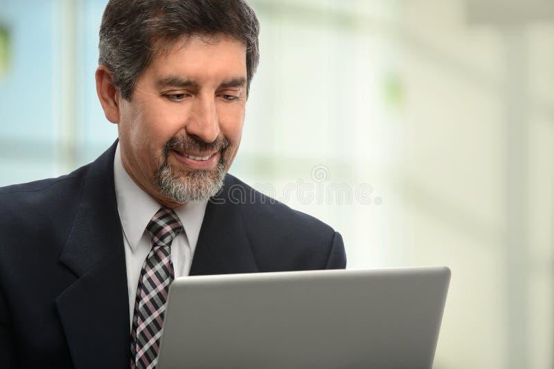 Uomo d'affari ispano Using Laptop fotografie stock