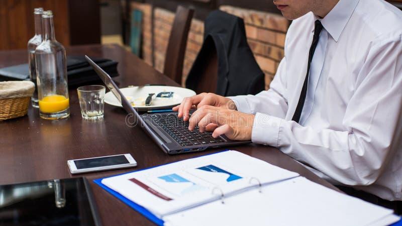 Uomo d'affari lavorante duro in ristorante. fotografie stock