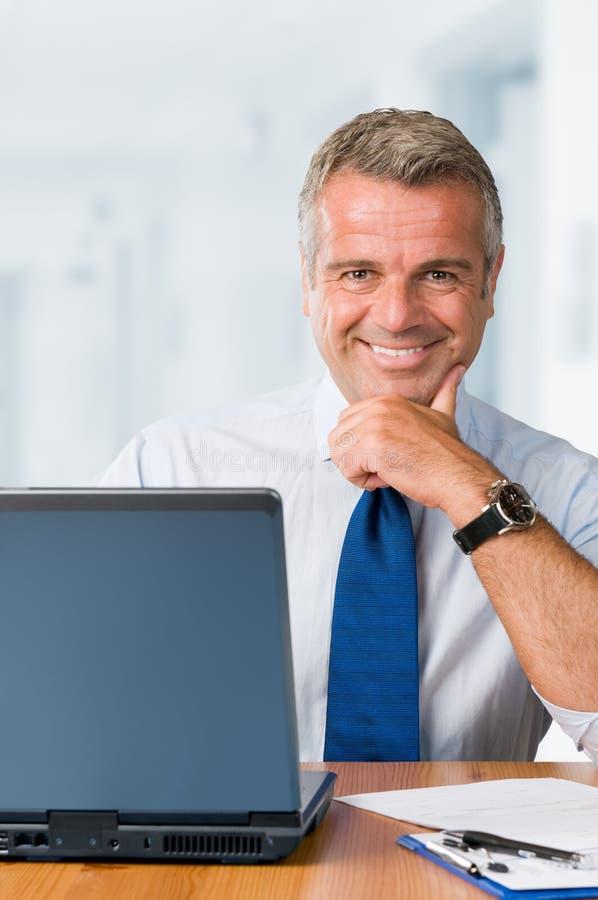 Uomo d'affari lavorante sorridente felice fotografia stock