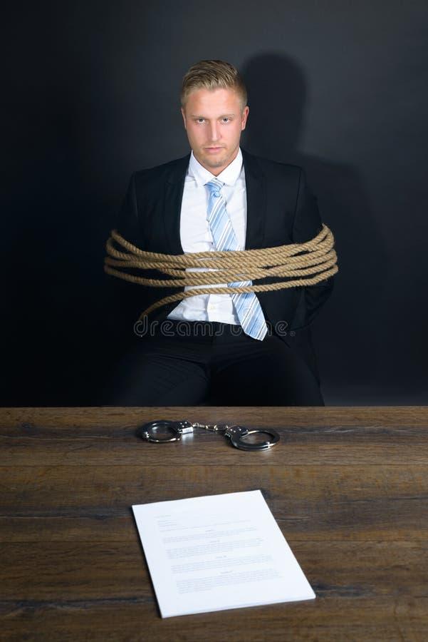 Uomo d'affari legato con la corda che si siede davanti alla tavola immagine stock