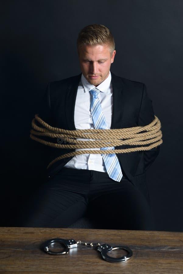 Uomo d'affari legato con la corda che si siede davanti alla tavola fotografia stock