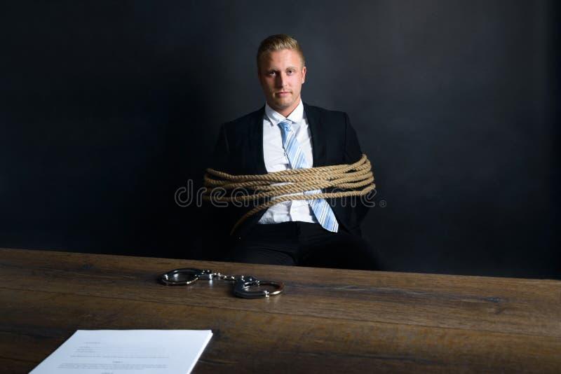 Uomo d'affari legato con la corda che si siede davanti alla tavola fotografia stock libera da diritti