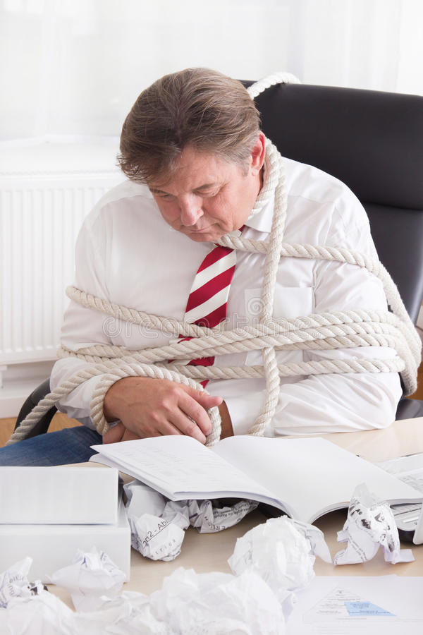 Uomo d'affari legato con la corda nell'ufficio. Lavoro senza estremità immagine stock libera da diritti