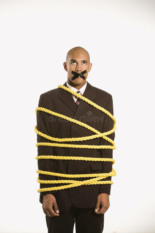 Uomo d'affari legato nella corda. fotografie stock