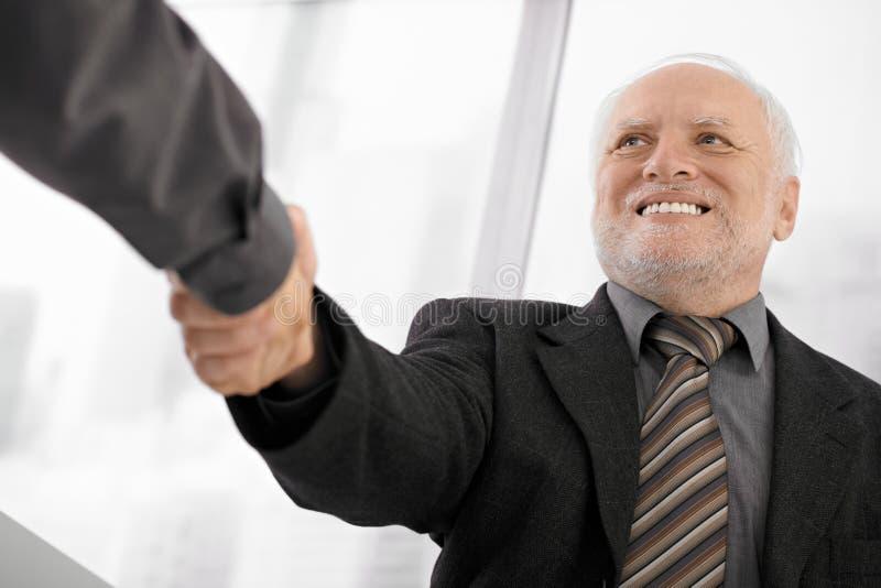 Uomo d'affari maggiore che agita le mani fotografia stock