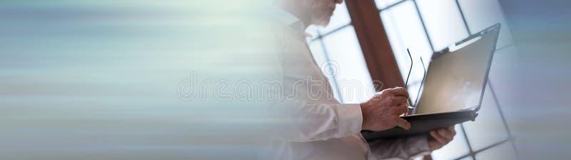 Uomo d'affari maggiore che lavora al computer portatile Bandiera panoramica immagini stock libere da diritti