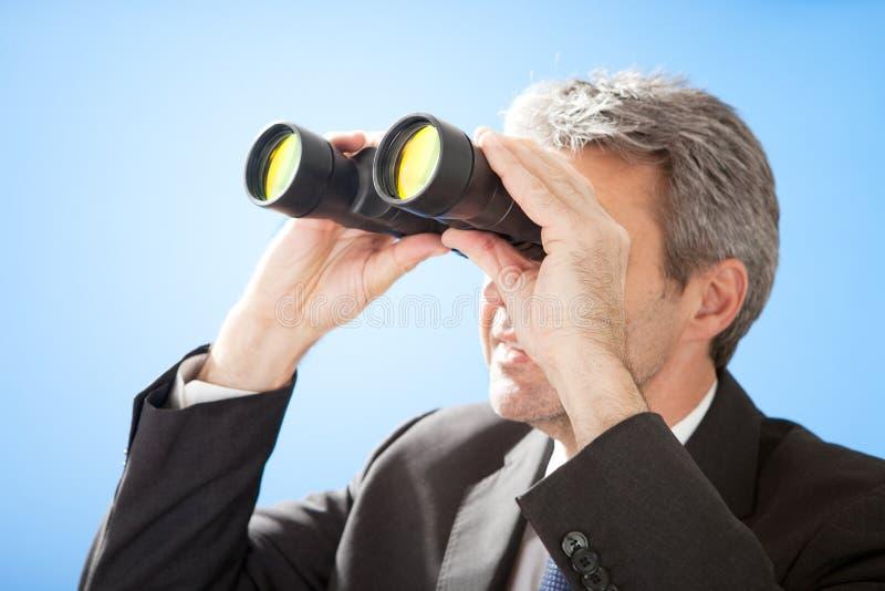 Uomo d'affari maggiore che osserva tramite il binocolo fotografia stock