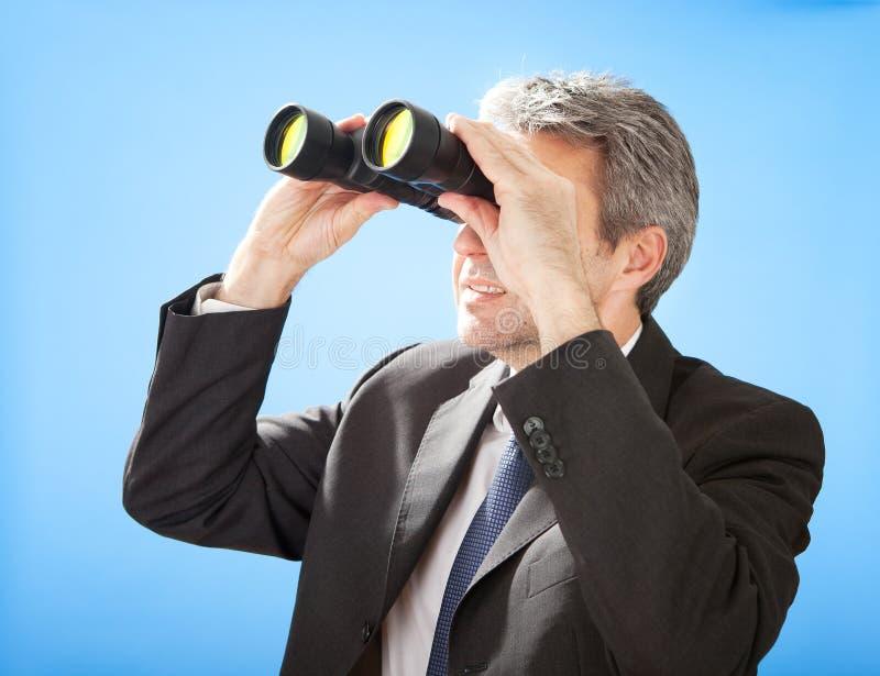 Uomo d'affari maggiore che osserva tramite il binocolo fotografie stock libere da diritti