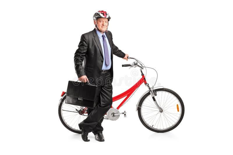 Uomo d'affari maggiore che propone vicino ad una bici fotografia stock