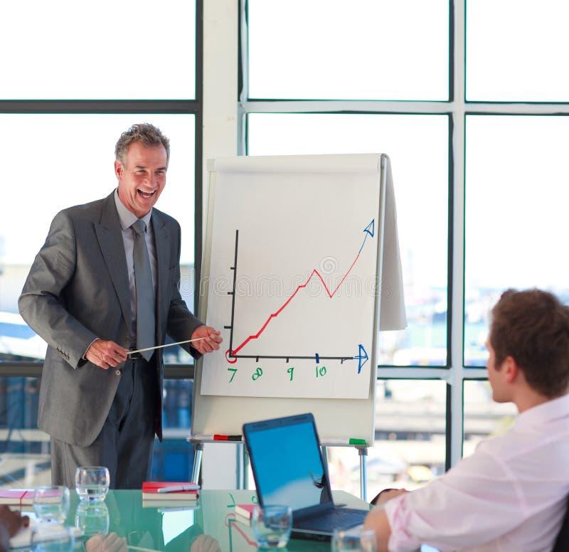 Uomo d'affari maggiore sorridente in una presentazione immagini stock libere da diritti