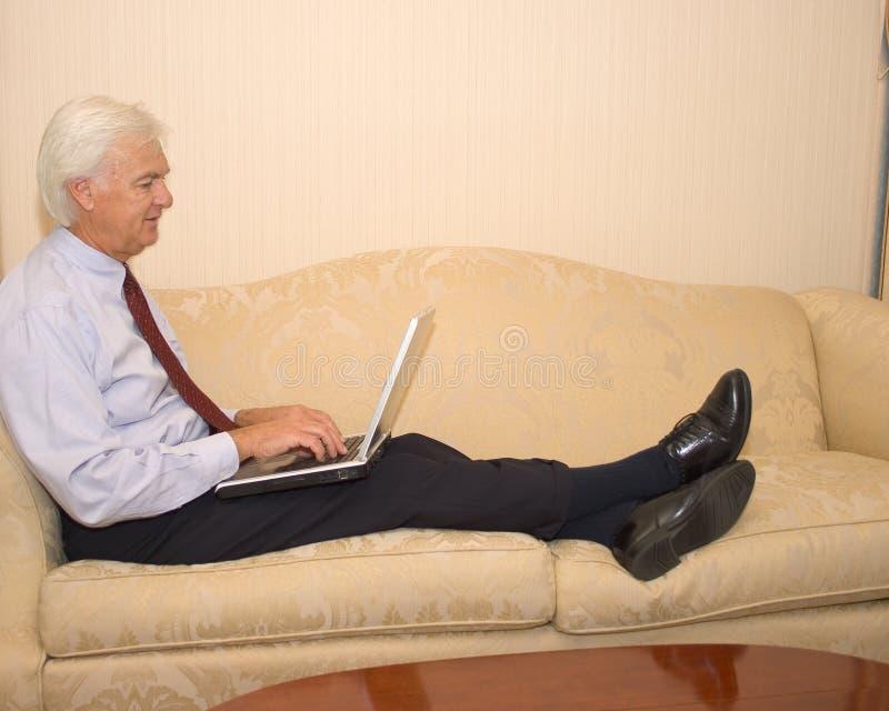 Uomo d'affari maggiore sul computer portatile fotografia stock