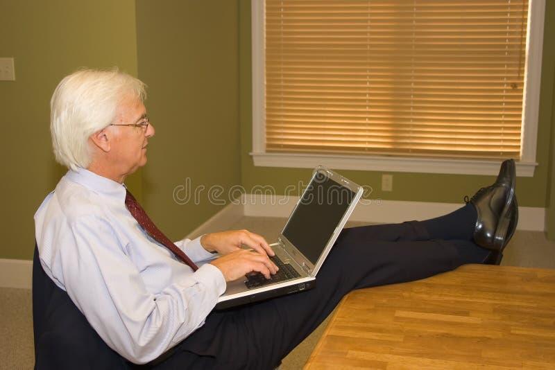 Uomo d'affari maggiore sul computer portatile immagini stock libere da diritti