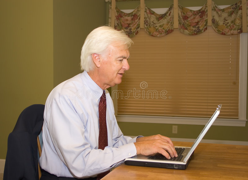 Uomo d'affari maggiore sul computer portatile fotografie stock libere da diritti